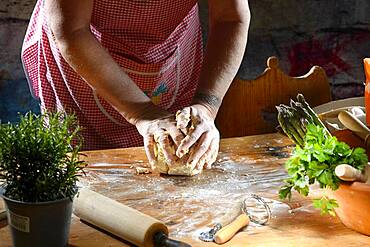 Cook kneading pasta dough for pasta on wooden table, Germany, Europe