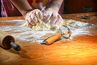 Cook kneading pasta dough on wooden table, Germany, Europe