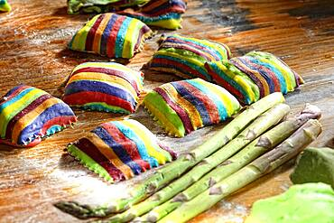 Homemade colorful ravioli on floured wooden table, Germany, Europe