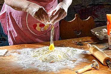 Cook making pasta dough on wooden table, flour and beaten egg, Germany, Europe