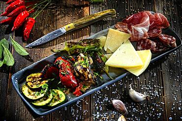Antipasti plate with vegetables, cheese, sausage and ham