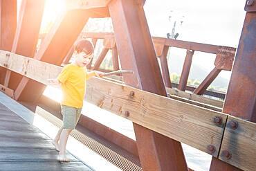 Mixed Race Chinese and Caucasian Boy Playing Alone on Bridge