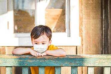 Young Mixed Race Chinese and Caucasian Boy Playing Alone Wearing Medical Face Mask Outside