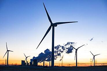Wind turbines in front of steaming coal-fired power plant at sunset, energy transition, fossil and renewable energy, Niederaussem, North Rhine-Westphalia, Germany, Europe