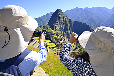 Tourists photograph the ruined city of the Incas and the mountain Huayna Picchu