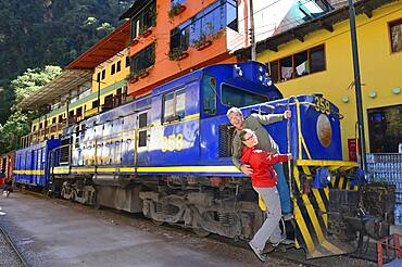 Two tourists at the locomotive of the Perurail in the station, Aguas Calientes, Machu Picchu, Urubamba Province, Peru, South America