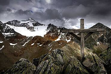 Summit cross at Falkengrat with Oetztal mountains and dramatic sky, Soelden, Oetztal, Tyrol, Austria, Europe