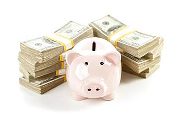 Pink piggy bank with stacks of hundreds of dollars isolated on a white background
