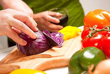 Man slicing vegetables on cutting board while woman enjoys a glass of red wine