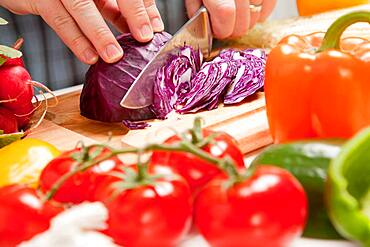 Man slicing vegetables on wooden cutting board