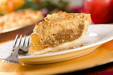 Apple pie slice with crumb topping and fork
