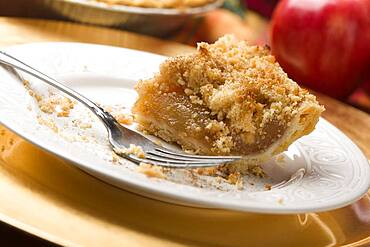 Half eaten apple pie slice with crumb topping and fork