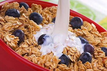 Milk being poured into bowl of granola and boysenberries