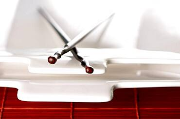 Wooden chopsticks & white plate on bamboo placemat