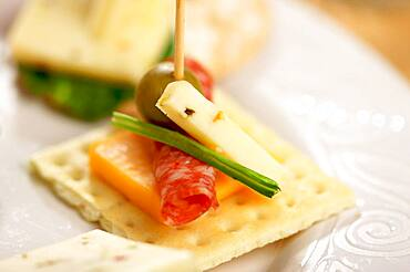 Cracker appetizers with cheese, olive and pepperoni