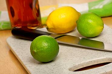 Limes, lemons and knife on cutting board