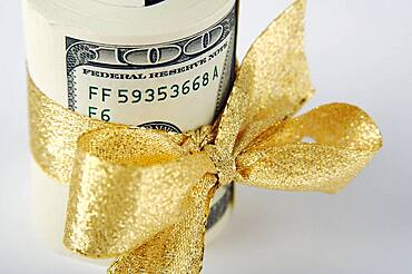 One hundred dollar bills wrapped in gold ribbon
