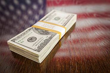 Thousands of dollars stacked with reflection of american flag on wooden table