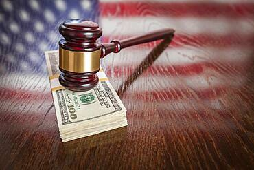 Wooden gavel resting on stack of money with american flag reflection on table