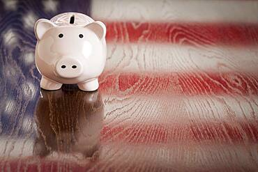 Piggy bank with an american flag reflection on wooden table