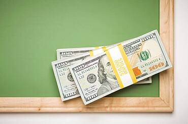 Newly designed U.S. one hundred dollar bills stacked on chalk board