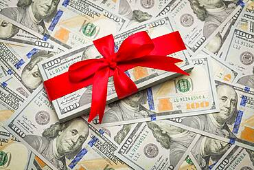 Stack of newly designed U.S. one hundred dollar bills gift wrapped in red bow