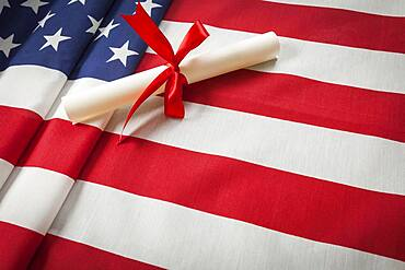 Red ribbon wrapped diploma resting on american flag with copy space