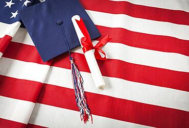 Graduation cap with tassel and red ribbon wrapped diploma resting on american flag