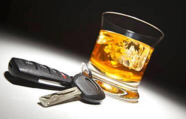 Alcoholic drink and car keys under spot light