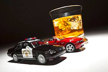 Police and sports car next to alcoholic drink under spot light