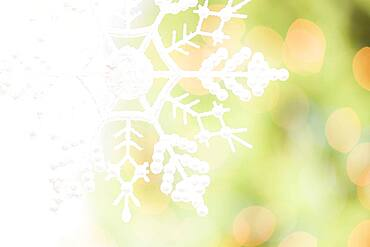 White glittery snowflake over an abstract green and gold background