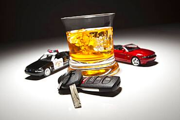Highway patrol police and sports car next to alcoholic drink and keys under spot light