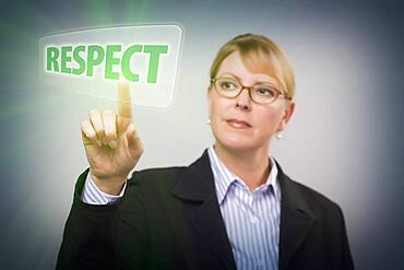 Attractive blonde woman pushing respect button on an interactive touch screen