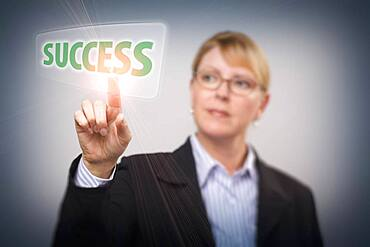 Attractive blonde woman pushing success button on an interactive touch screen, focus is on her finger