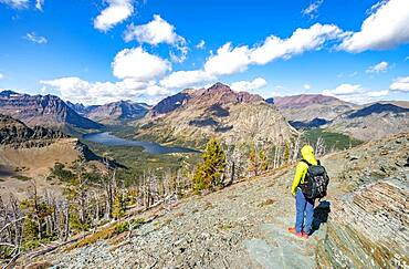 Hikers on the trail to Scenic Point, view of Two Medicine Lake, mountain peaks Rising Wolf Mountain and Sinopah Mountain, Glacier National Park, Montana, USA, North America