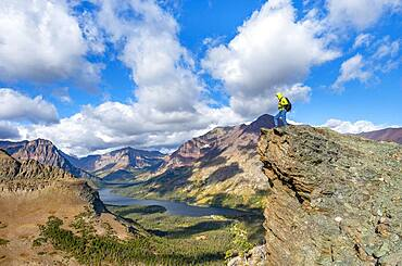Hiker standing on rock ledge, view of Two Medicine Lake, mountain peaks Rising Wolf Mountain and Sinopah Mountain, hiking trail to Scenic Point, Glacier National Park, Montana, USA, North America