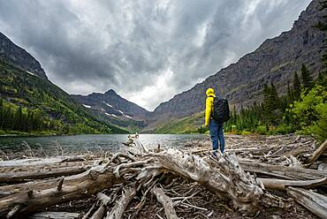Hikers at Upper Two Medicine Lake, mountain peak Lone Walker Mountain in the back, dramatic clouds, Glacier National Park, Montana, USA, North America