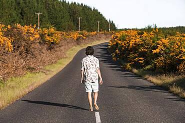 Guy walking on a road, Rotorua, Bay of Plenty, North Island, New Zealand, Oceania