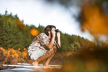 Guy with camera on car roof, Rotorua, Bay of Plenty, North Island, New Zealand, Oceania