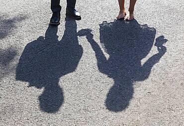 Shadow image of bride and groom on asphalt path, Germany, Europe