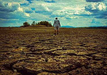 Man standing at cracked earth at the bottom dried up lake, Poland, Europe