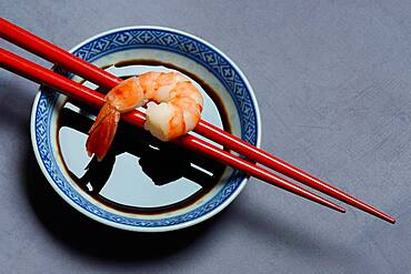 Cooked shrimp on chopsticks and shell with soy sauce, Germany, Europe