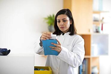 Pharmacist with medicine in a pharmacy working with modern technology and smock, Freiburg, BW