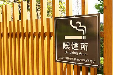 Wooden fence with smoking area sign in a business district in Tokyo, Japan, Asia