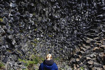 Woman in front of column basalt, Echo Rock Hljooaklettar, Vestudalur, North Iceland, Iceland, Europe
