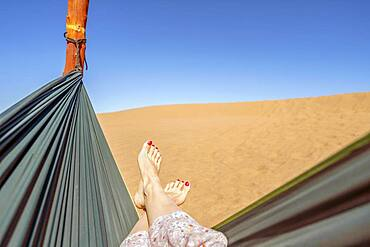Young woman relaxing in green hammock with view on sand dunes of Sahara Desert, Morocco, Africa