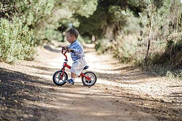 Cute toddler riding his bicycle on the dirt road