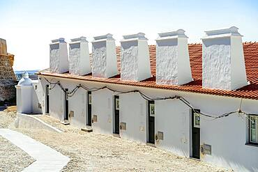 Traditional residential terraced houses with huge chimneys next to castle in Campo Maior, Alentejo, Portugal, Europe