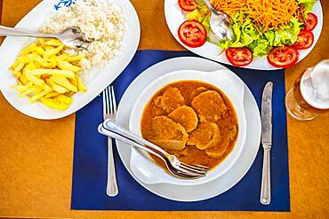 Traditional food from Alentejo, cow's tongue in a sauce served with salad, rice and french fries, Portugal, Europe