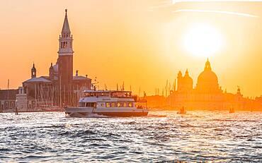 Vaporetto, water bus driving on the lagoon of Venice, evening mood, island Isola di San Giorgio Maggiore with church San Giorgio Maggiore, Basilica Santa Maria della Salute, Venice, Veneto, Italy, Europe